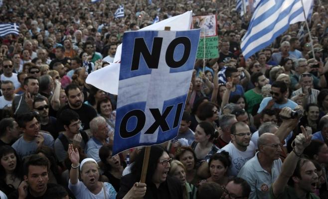 """Un protestatar poartă un panou pe care scrie OXI (""""oxi"""" înseamnă """"nu"""" în limba română)."""