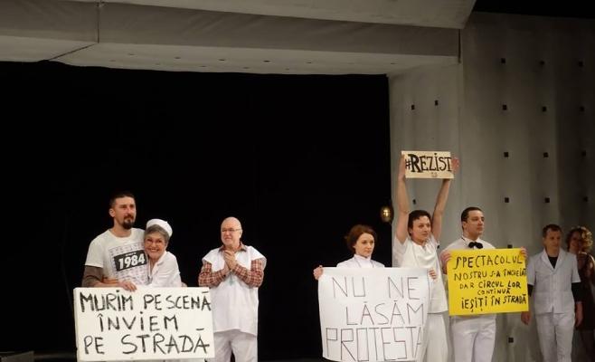 Mai mulţi actori ai Teatrului Naţional au afişat mesaje de solidarizare cu protestatrii, după unul din spectacole. Ionuţ Caras (primul din stânga) a fost principalul promotor al acţiunii. FOTO Facebook