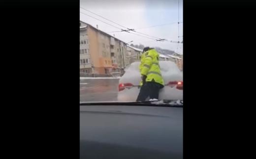 Mereu la datorie! Polițiștii au dat jos zăpada de pe lunetele șoferilor, dar nu au scos și carnețelul de amenzi. VIDEO
