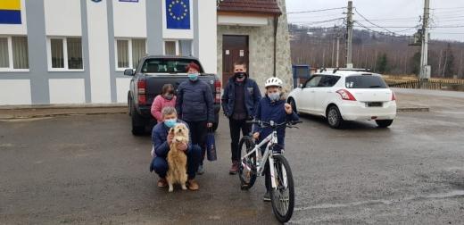 Voluntarii de la CERT i-au dăruit o bicicletă nouă băiatului care a tras cu sania un câine în Râșca