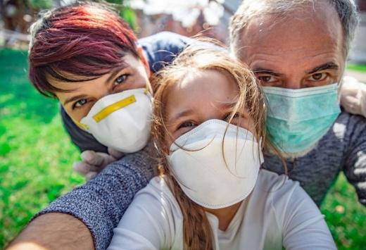 Familie împreună, purtând masca de protecție, în pandemia de COVID